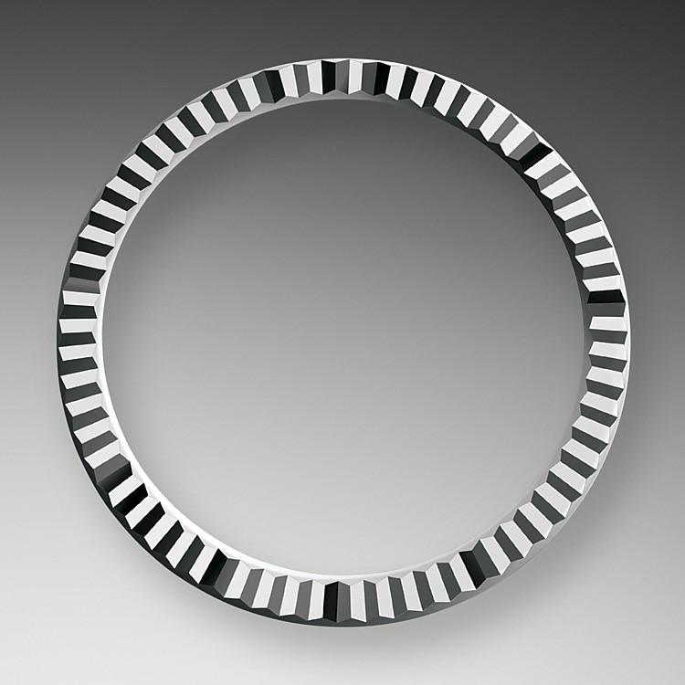 Die geriffelte Rolex Lünette ist ein Distinktionsmerkmal. Ursprünglich hatte die Riffelung der Oyster Lünette einen praktischen Zweck: Sie diente zum Verschrauben mit dem Gehäusemittelteil, um die Wasserdichtheit der Uhr zu gewährleisten. Die Riffelung entsprach deshalb der des Gehäusebodens, der ebenfalls mithilfe von Rolex Spezialwerkzeugen mit dem Mittelteil verschraubt wurde, um die Uhr wasserdicht zu machen. Mit der Zeit erhielt die Riffelung eine rein ästhetische Funktion und wurde zu einem charakteristischen Markenzeichen einer Rolex. Heute ist die geriffelte Lünette ein Distinktionsmerkmal, das ausschließlich in Gold gefertigt wird.