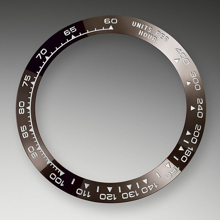 Dank seiner charakteristischen gravierten Lünette mit Tachymeterfunktion ist dieses Modell imstande, Durchschnittsgeschwindigkeiten bis zu 400Meilen oder Kilometern pro Stunde zu messen. Bei der schwarzen Lünette verbindet sich Spitzentechnologie mit gefälliger Ästhetik und sie erinnert an das Modell von 1965 mit seiner schwarzen Plexiglas-Zahlenscheibe. Die Monoblock-Tachymeterlünette aus Hightechkeramik bietet zahlreiche Vorteile: Aufgrund ihrer Härte ist sie nicht nur äußerst kratzfest, sondern in der Farbe auch UV-resistent und korrosionsbeständig. Zu der extremen Langlebigkeit kommt die außerordentlich gute Ablesbarkeit der Ziffern auf der Tachymeterskala hinzu. Die Graduierung wird zunächst in der Keramikmasse ausgebildet und dann im PVD-Verfahren (Physical Vapour Deposition, physikalische Gasphasenabscheidung) mit einer feinen Platinschicht überzogen. Die aus einem Teil bestehende Monoblock-Cerachrom-Tachymeterlünette gewährleistet die Wasserdichtheit und den festen Sitz des Uhrglases auf dem Mittelteil.